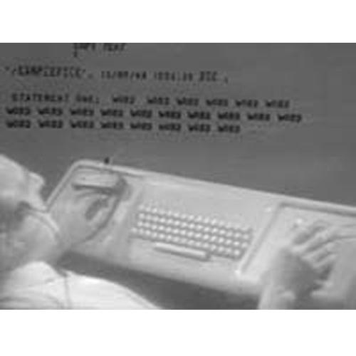 photo Doug interacting with computer display using mouse, keyset, headset